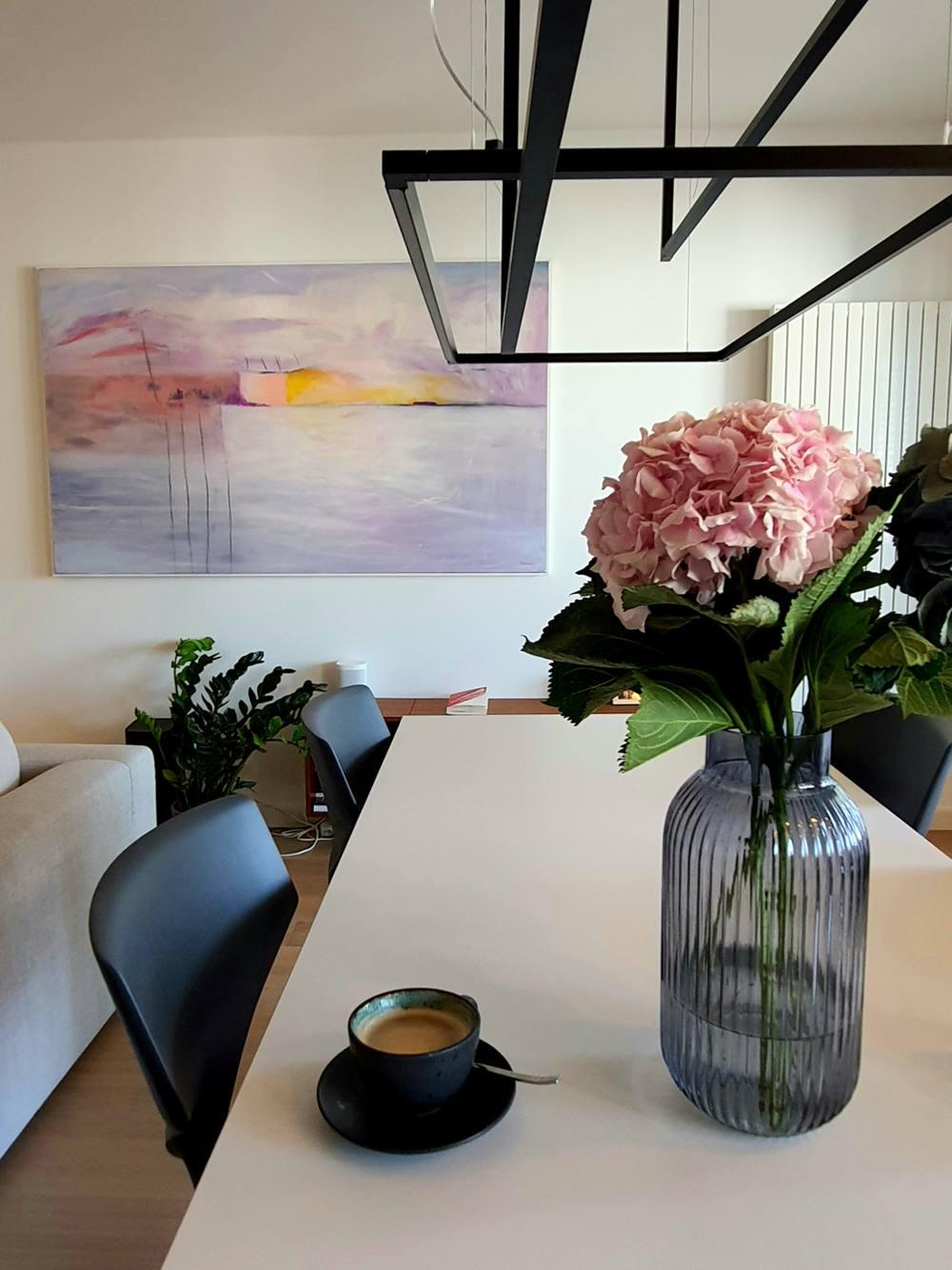 Cvijeće u vazi, kava na stolu i pogled na veliku apstraktnu sliku Ajdinović Ranka u Zagrebu
