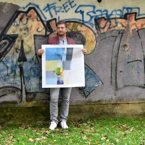 Ajdinović Ranko slikar drži u ruci umjetničku sliku grafiku giclee